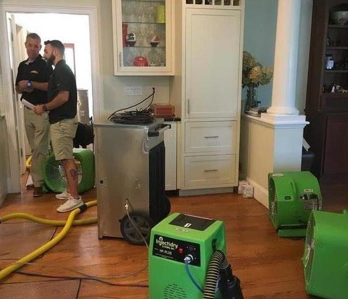 2 men standing in house with green equipment set out