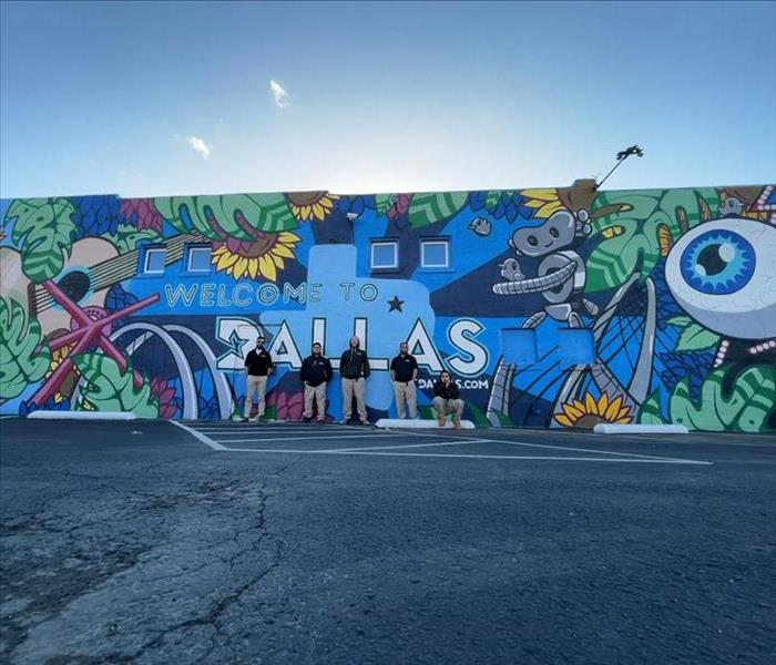 SERVPRO technicians posing in front of Dallas, Texas graffiti mural